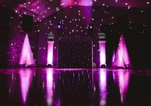 DJ Booth with purple lighting in front of a star cloth