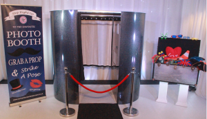Enclosed photo booth with black carpet and box of props
