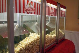 Three popcorn machines with popcorn inside