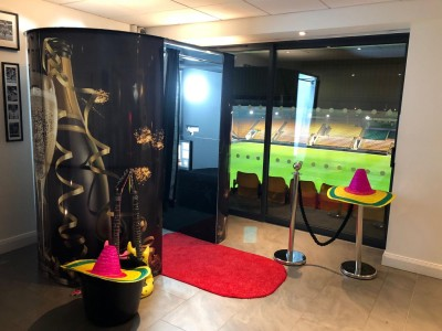 Photobooth with champagne theming with a red carpet, rope barriers and props
